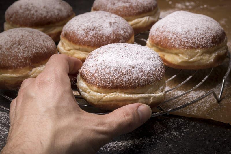 采取鲜美多福饼的男性手 免版税图库摄影
