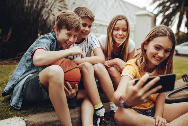 采取selfie的孩子坐户外 免版税库存图片