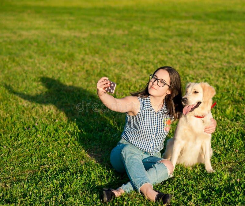 采取selfie的少妇和她友好的狗在公园 图库摄影
