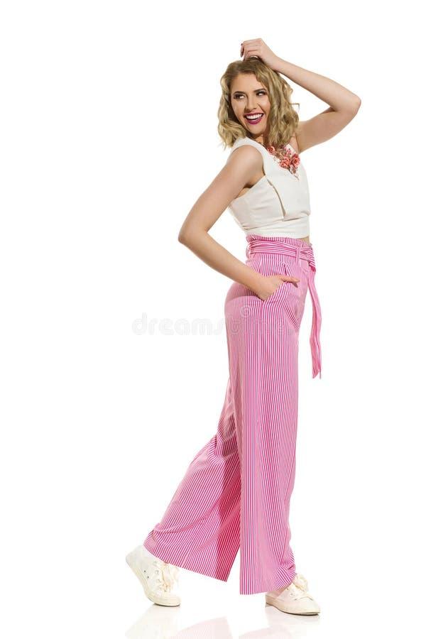 镶边宽腿长裤的妇女看在肩膀和笑 免版税库存图片