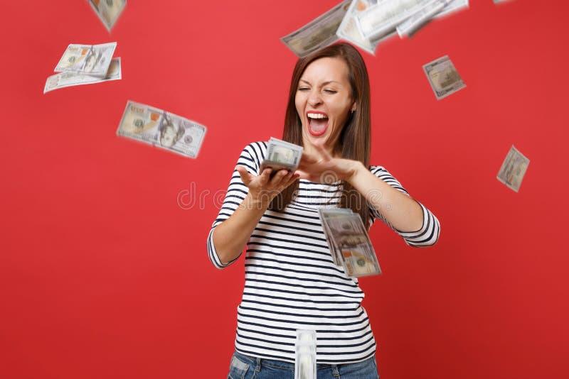镶边衣裳的尖叫疯狂的妇女驱散把金钱在明亮的红色隔绝的钞票许多美元扔出去 库存照片