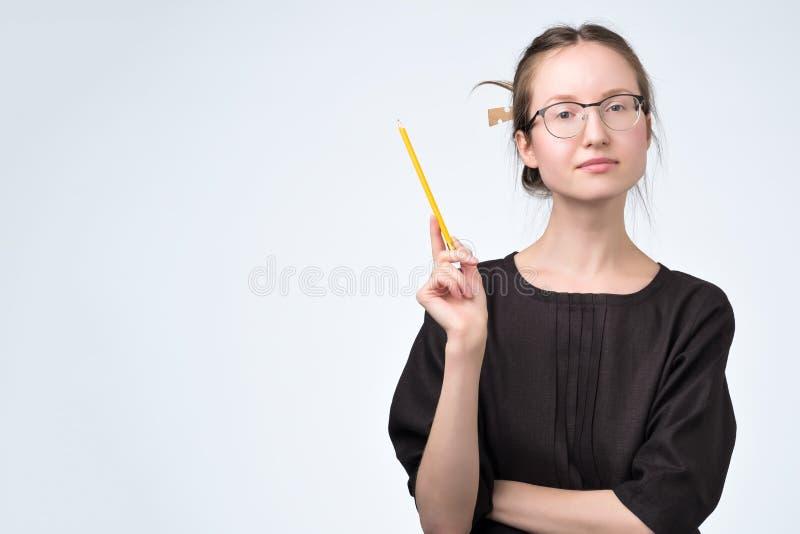 镜片的妇女在提建议的黑礼服有一个好想法 免版税库存照片