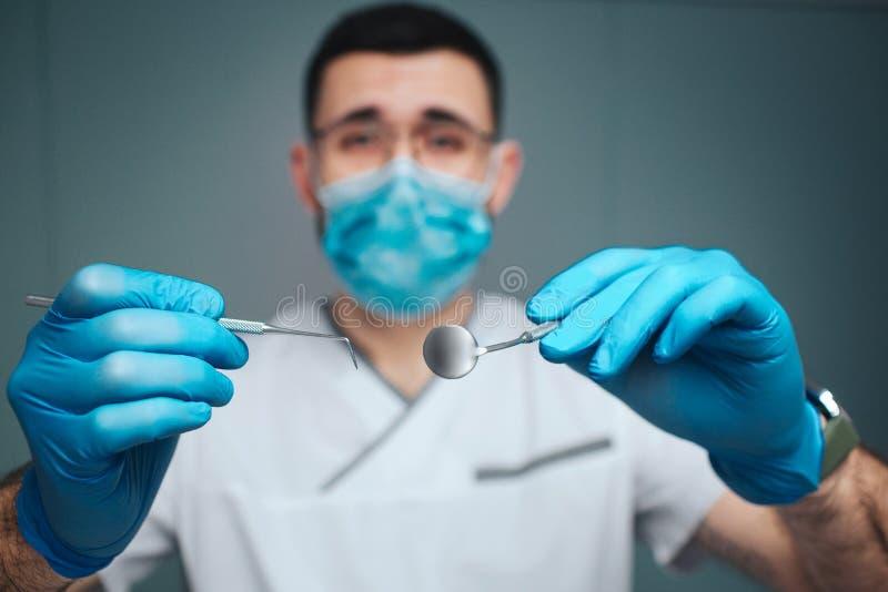 镇静平安的年轻人做制服和面具的牙医 他在照相机看并且拿着牙齿工具 人穿戴乳汁手套 免版税库存照片