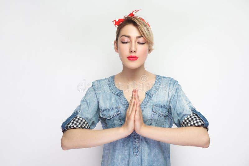镇静美丽的年轻女人画象偶然蓝色牛仔布衬衣的有构成和红色头饰带身分的用棕榈手和 库存照片