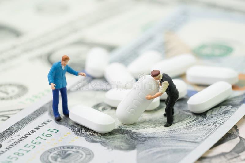 配药,医疗保健和医学工业企业概念,微型工作者设法移动在美元的白色片剂药片 库存照片
