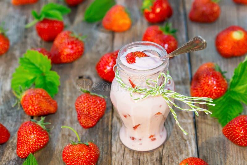 酸奶用在一个瓶子的新鲜的草莓有匙子的 选择聚焦 库存照片