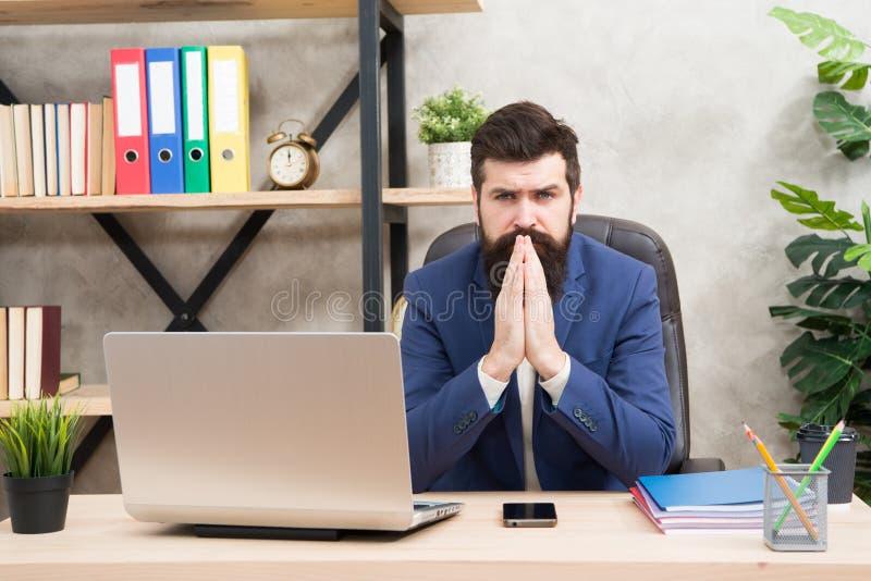 集中主要任务 人有胡子的上司坐有膝上型计算机的办公室 解决业务问题的经理 商人 库存图片