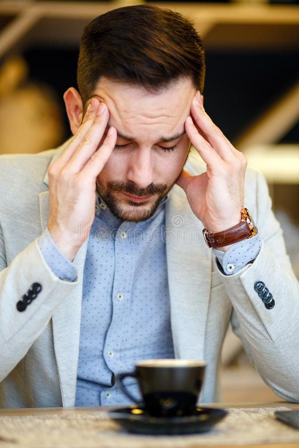 集中劳累过度的年轻的商人有头疼和,当喝一杯咖啡时 库存图片