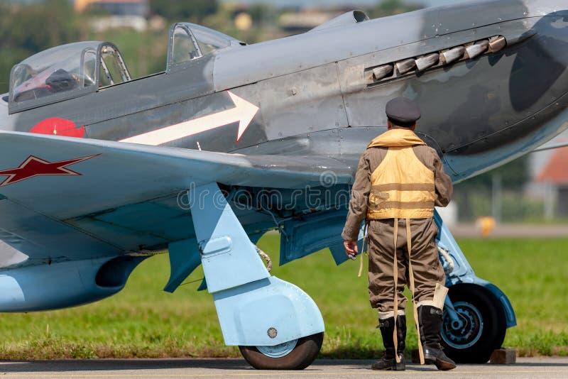 雅科航空器集团牦牛3M二战有在期间制服打扮的飞行员的战机D-FYGJ 免版税库存图片
