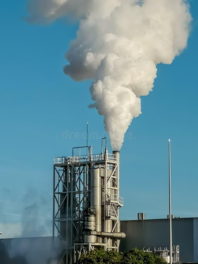 逐出很多烟的工业烟囱 免版税库存图片