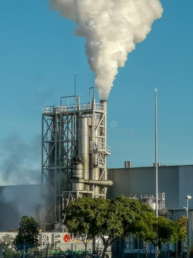 逐出很多烟的工业烟囱 图库摄影