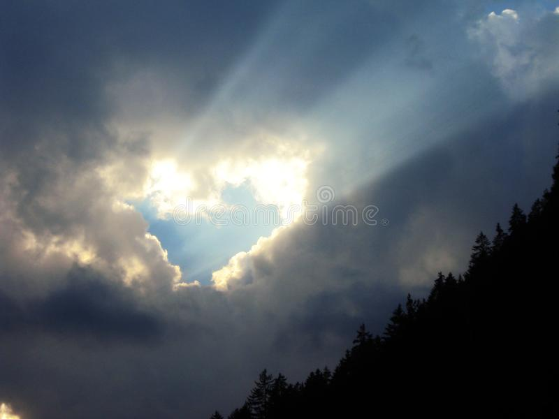 通过天堂般的心脏的云彩击穿平衡的太阳的光芒 免版税图库摄影