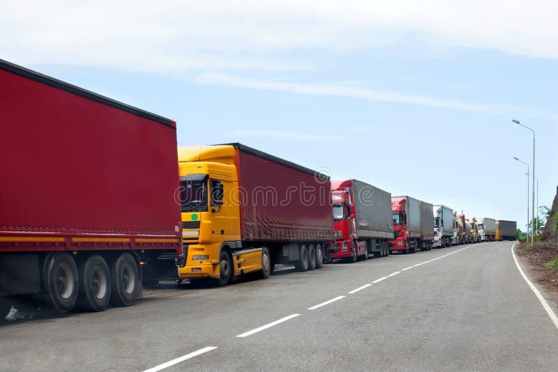 通过在堵车的卡车队列国境、红色和不同颜色卡车在路 库存照片
