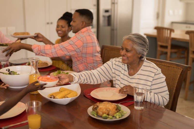 通过食物的资深妇女对她的在dinning的桌上的孙子 免版税库存照片