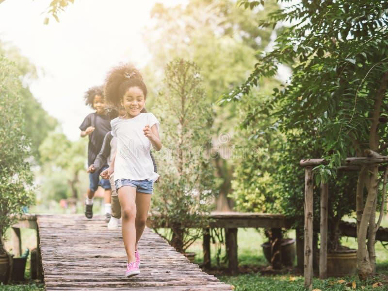 逗人喜爱小女孩使用室外 在公园的孩子和朋友愉快的戏剧 免版税库存图片
