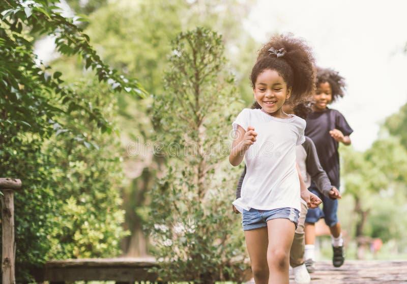逗人喜爱小女孩使用室外 在公园的孩子和朋友愉快的戏剧 免版税库存照片