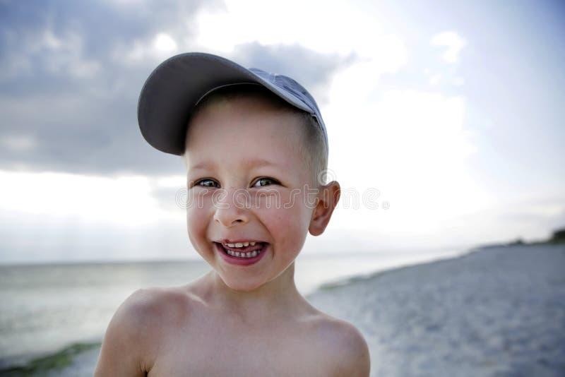 逗人喜爱微笑海海滩的小男孩 免版税库存照片