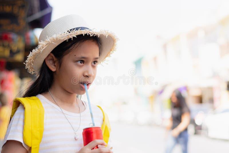 逗人喜爱的女孩旅客喝着在thalang路,普吉岛,泰国的冷的汽水 免版税图库摄影