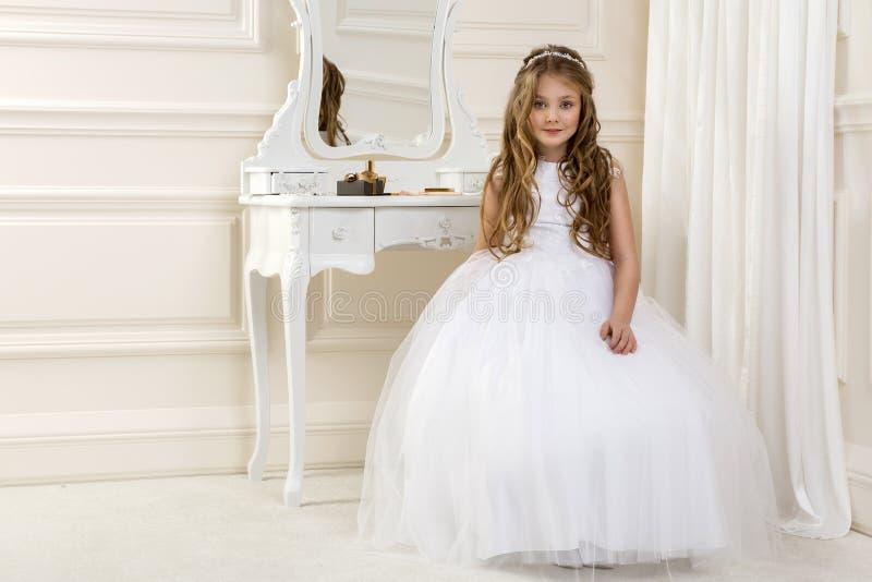 逗人喜爱的女孩画象白色礼服和花圈的在第一个圣餐背景教会门 免版税图库摄影
