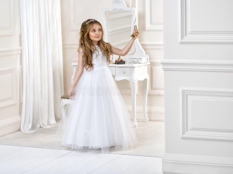 逗人喜爱的女孩画象白色礼服和花圈的在第一个圣餐背景教会门 库存图片