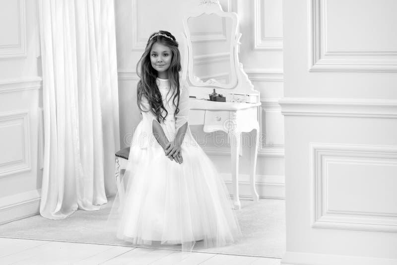 逗人喜爱的女孩画象白色礼服和花圈的在第一个圣餐背景教会门 免版税库存照片
