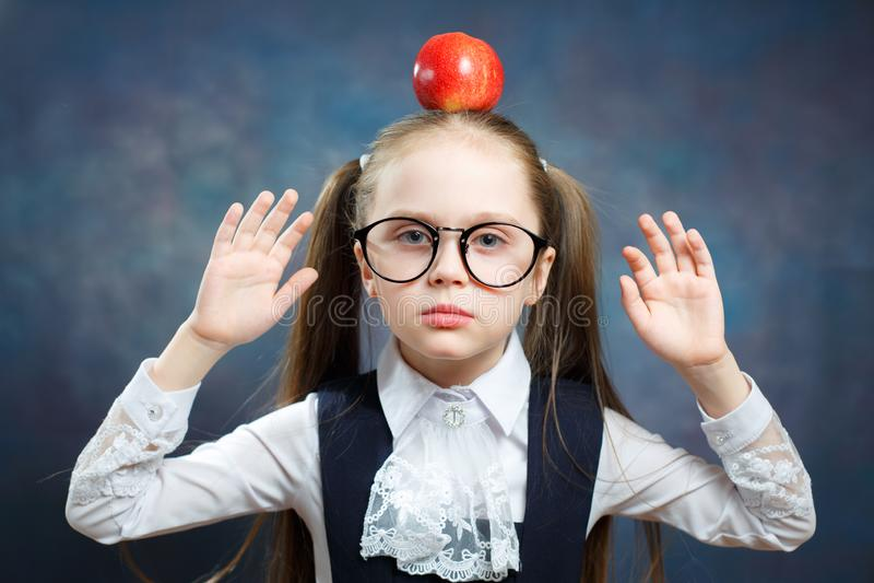 逗人喜爱的女小学生穿戴玻璃拿着在头的苹果计算机 免版税库存图片