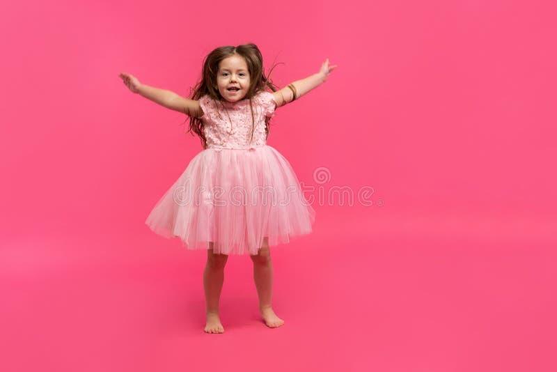 逗人喜爱的小女孩梦想成为芭蕾舞女演员 舞女一点 在桃红色背景的演播室射击 库存图片