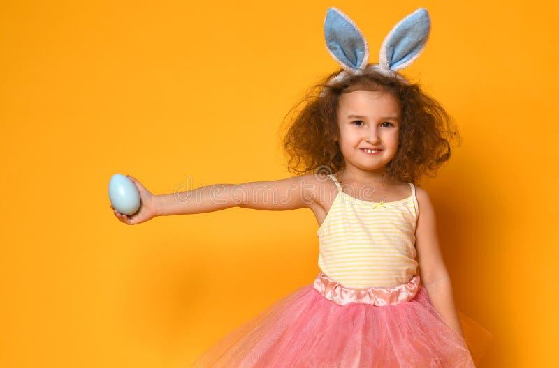 逗人喜爱的小孩女孩佩带的兔宝宝耳朵在复活节天 免版税库存照片
