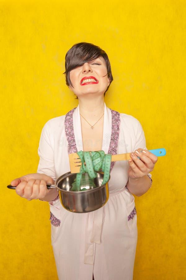 逗人喜爱的情感浅黑肤色的男人是饿的,设法跟随减肥的饮食 妇女在一件桃红色长袍站立,拿着一个空的罐 免版税库存图片