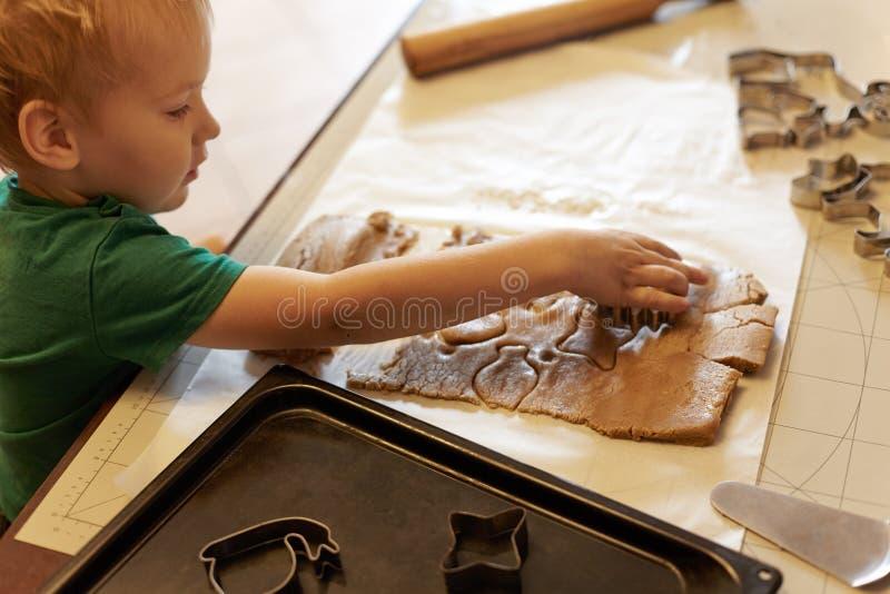 逗人喜爱的白种人男婴在厨房里帮助,做自创coockies 在家庭内部,俏丽的孩子,假日conce的偶然生活方式 库存图片