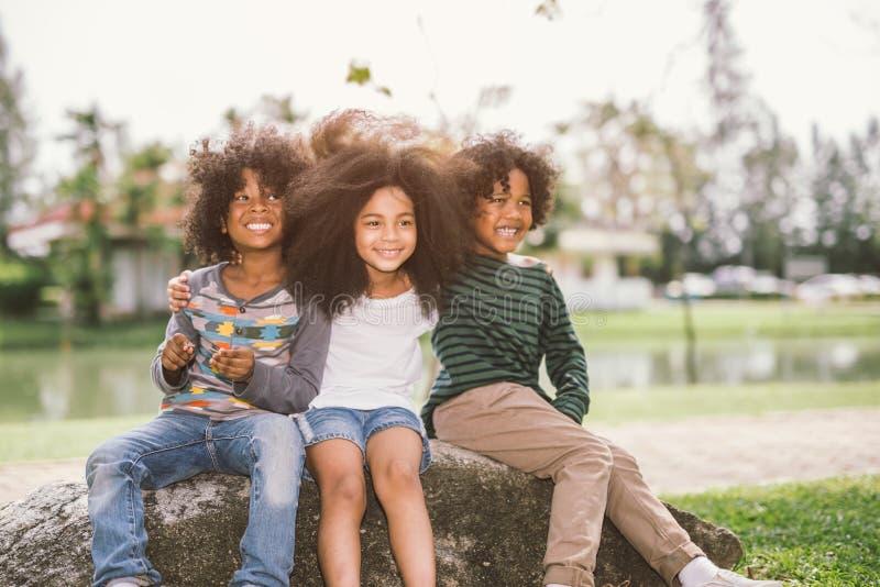 逗人喜爱的非裔美国人的小男孩和女孩在夏天晴天互相拥抱 库存照片