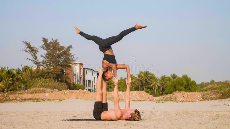 适合的运动的与伙伴的夫妇实践的acro瑜伽一起在沙滩 免版税库存照片