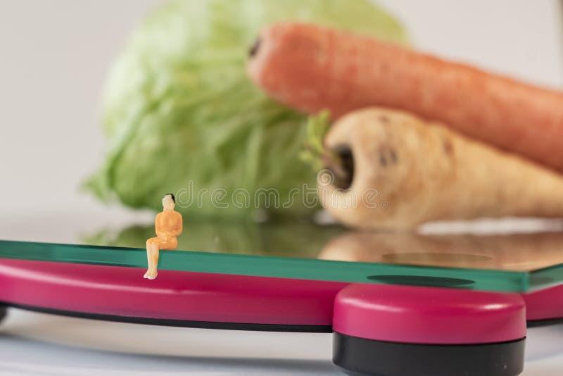 选址微型妇女的形象在重量的数字电子体重计人体 在浅深度的新鲜蔬菜 库存照片