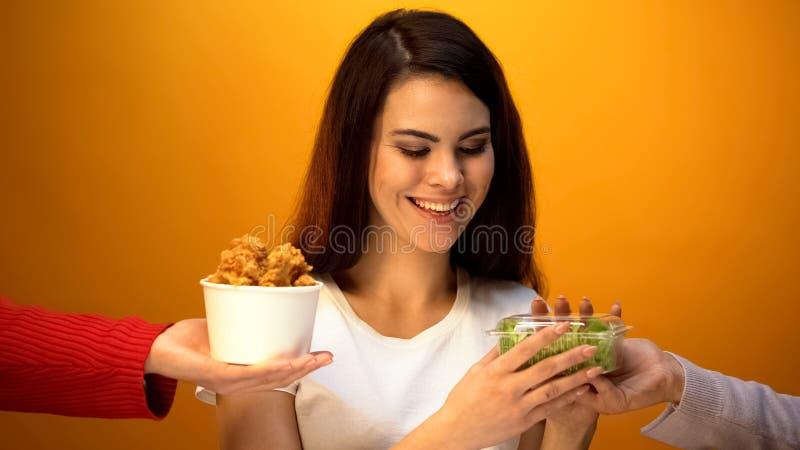 选择沙拉的女孩而不是油煎的肉,weightloss的健康食品,饮食 免版税库存图片