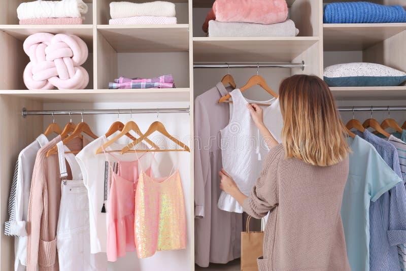选择成套装备的妇女从与时髦的衣裳的大衣橱壁橱 图库摄影