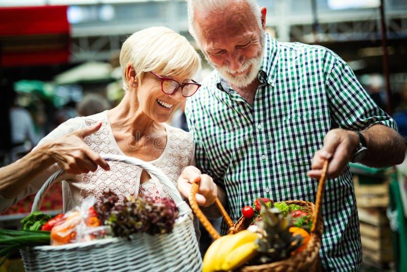 选择生物食物水果和蔬菜在市场上的资深家庭夫妇在每周购物期间 免版税库存图片