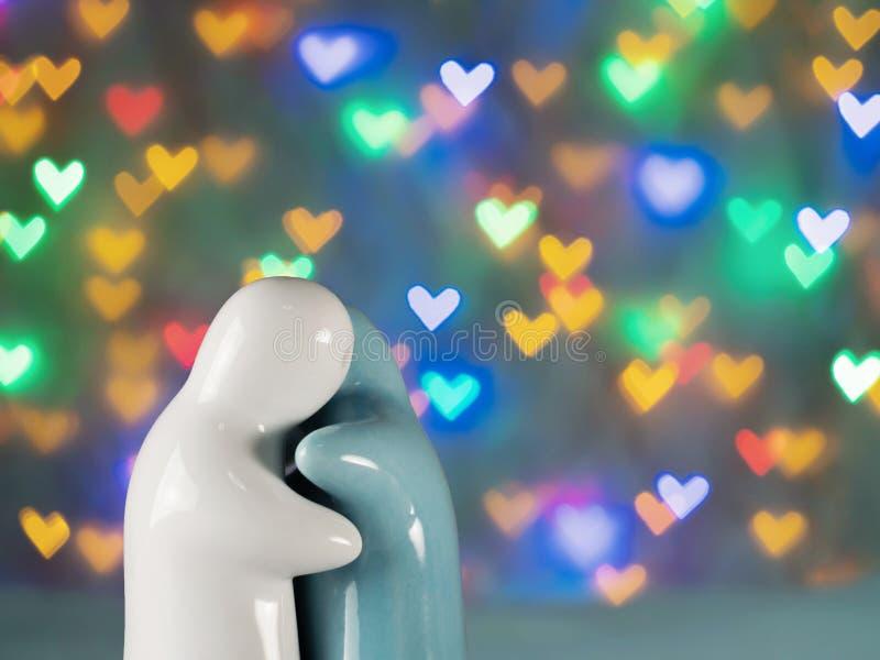 陶瓷玩偶,夫妇在美好的心形的bokeh背景一起拥抱 对于华伦泰 免版税库存图片