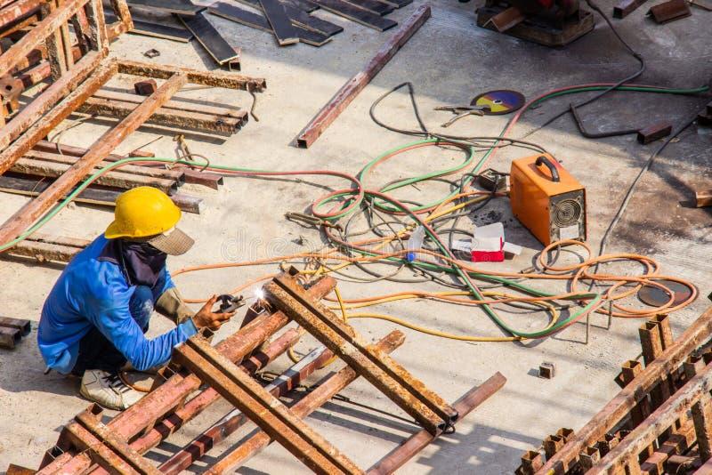 钢厂建筑的工业焊接的工作者与焊接的过程的区域大厦的由被保护的金属电弧焊接 库存图片