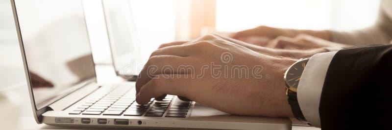 键入在计算机手和键盘特写镜头上的水平的图象商人 免版税库存照片