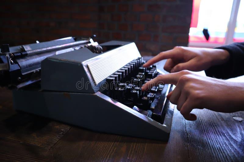 键入在葡萄酒打字机的手 免版税库存图片