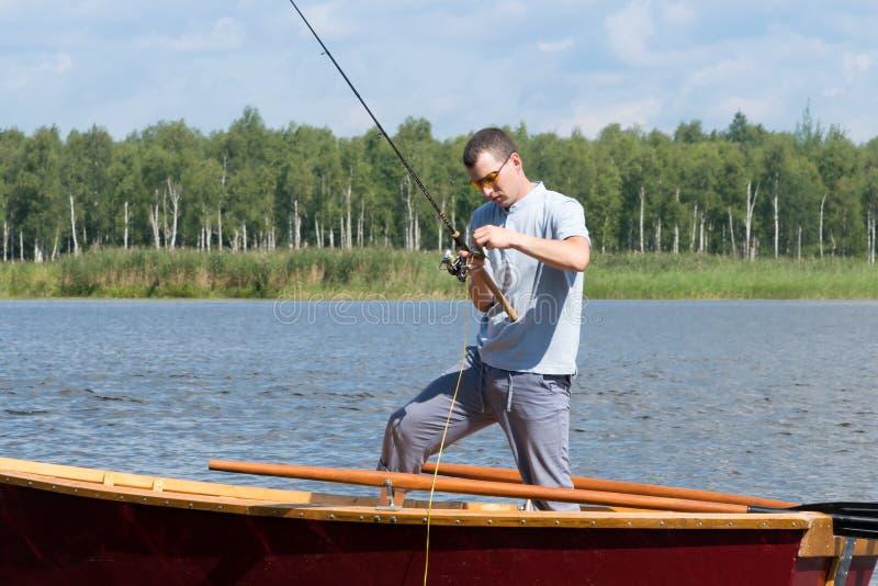 钓鱼在从小船的水到转动的特写镜头,室外活动 免版税库存照片