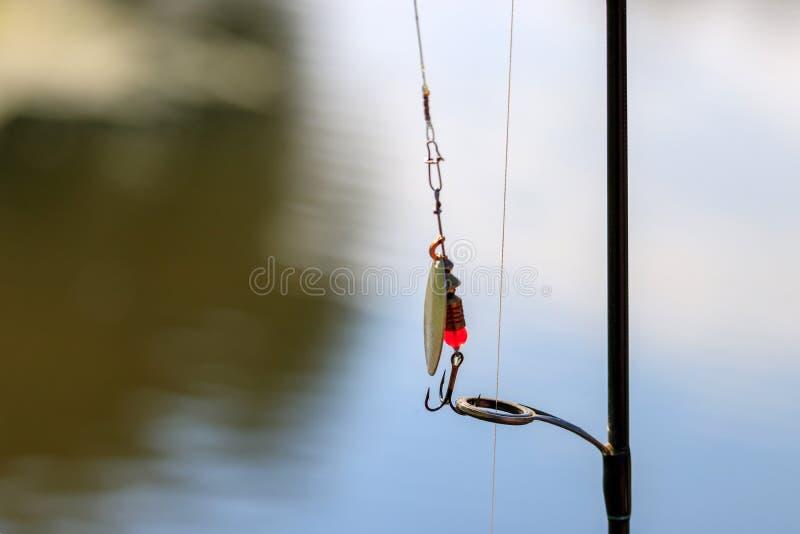 钓鱼诱剂和实心挑料铁杆特写镜头在水表面背景  库存图片