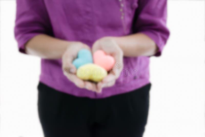 É borrado do coração colorido do artesanato da posse 3 da mulher em sua mão imagens de stock