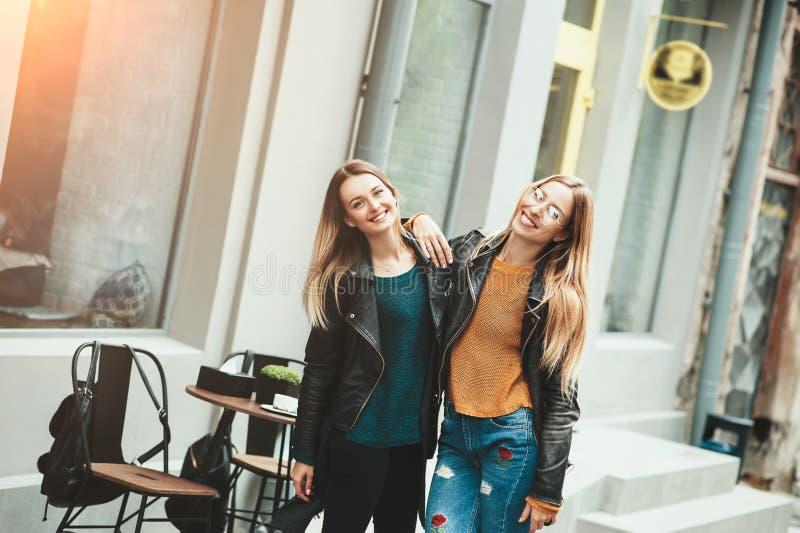 É caminhada engraçada com melhor amigo! Aperto exterior de passeio de duas mulheres bonitas e riso na rua do outono fotografia de stock