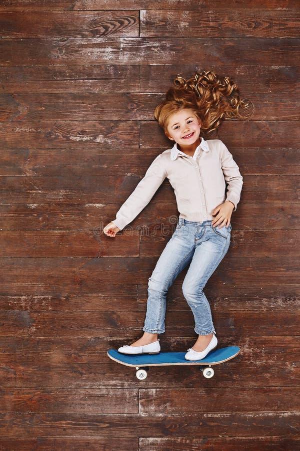 É divertimento que é uma criança Menina em um skate, encontrando-se no assoalho, olhando a câmera e o sorriso imagens de stock royalty free