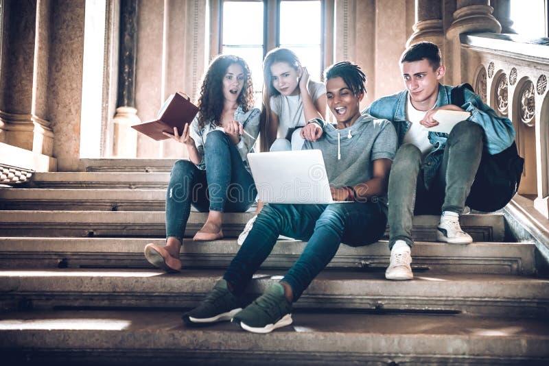 É inacreditável! Grupo surpreendido de estudantes que olham o portátil e que mantêm-se o quando aberto da boca ao sentar-se nas e fotos de stock