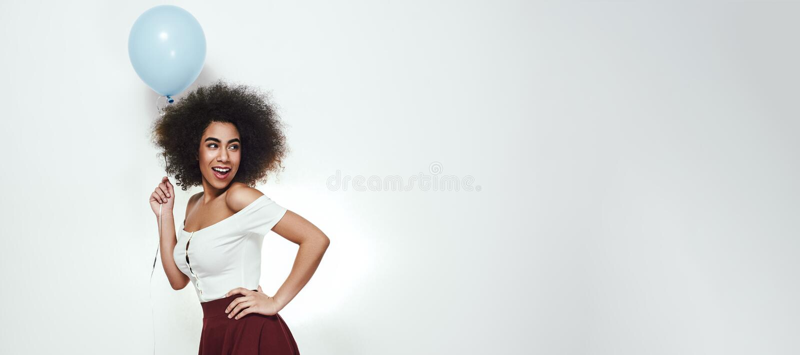 É meu partido! A mulher afro-americana feliz e bonita está guardando o balão azul, está mantendo o braço no quadril e está olhand imagem de stock royalty free