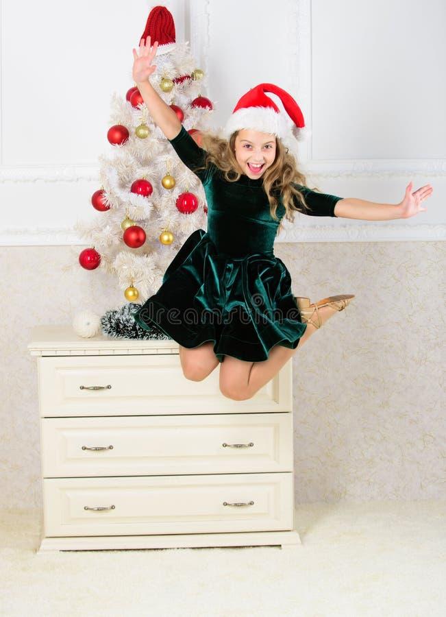 É Natal Dia onde nós esperamos todo o ano finalmente aqui Menina excitada sobre o meio do ar do salto do Natal Criança imagem de stock royalty free