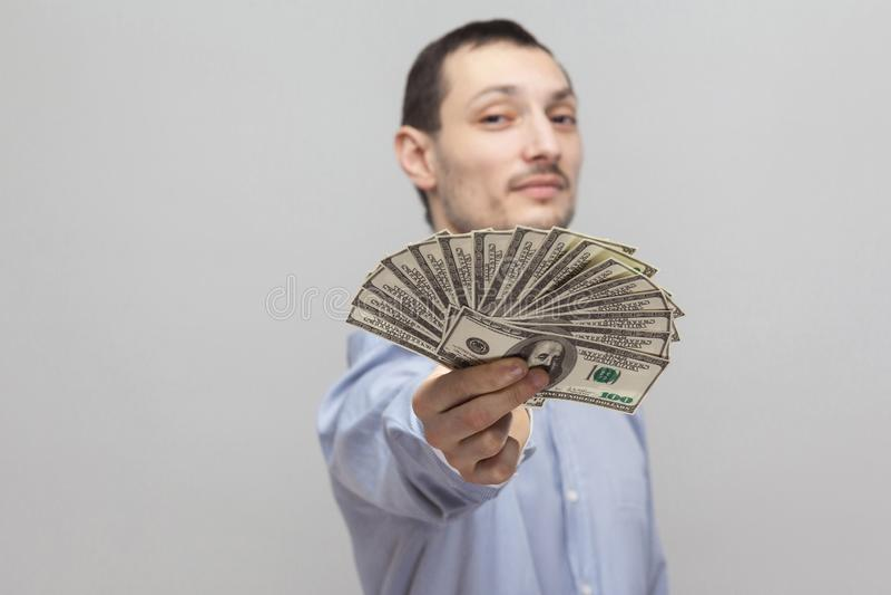 É para você! Retrato do homem de negócios adulto novo atrativo seguro satisfeito na camisa azul que está, mostrar, dando lhe o fã foto de stock royalty free