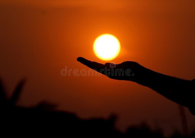 É possível segurar o sol sobre a mão, mas é possível captar o sol como na foto fotos de stock royalty free